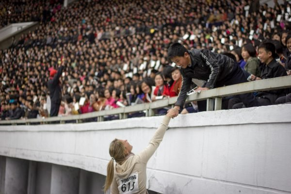 Foreigner shakes the hand of a North Korean spectator