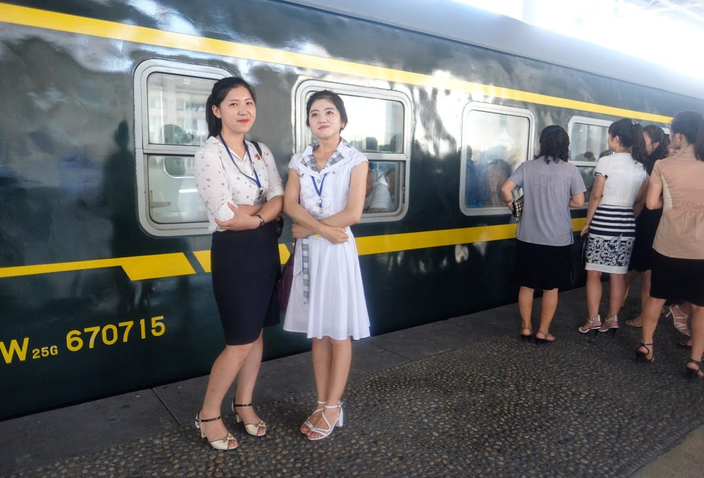 Two North Korean Tour guides at Pyongyang train station after a north korea tour