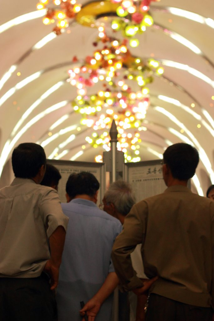 North koreans read the Rodong sinmun on the Pyongyang metro