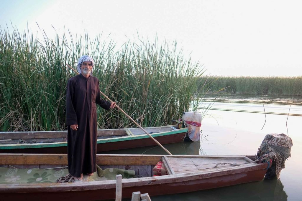 Boatman ferrying reeds in the marshes of Iraq